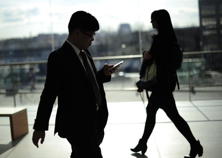 Image: A man uses a mobile device.