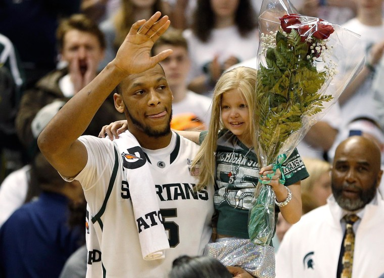 Adreian Payne #5 of the Michigan State Spartans walks on the floor for Senior night with Lacey Holsworth, a 8-year-old from St. Johns Michigan who is battling cancer, after defeating the Iowa Hawkeyes 86-76 at the Jack T. Breslin Student Events Center on February 6, 2014 in East Lansing, Mich.