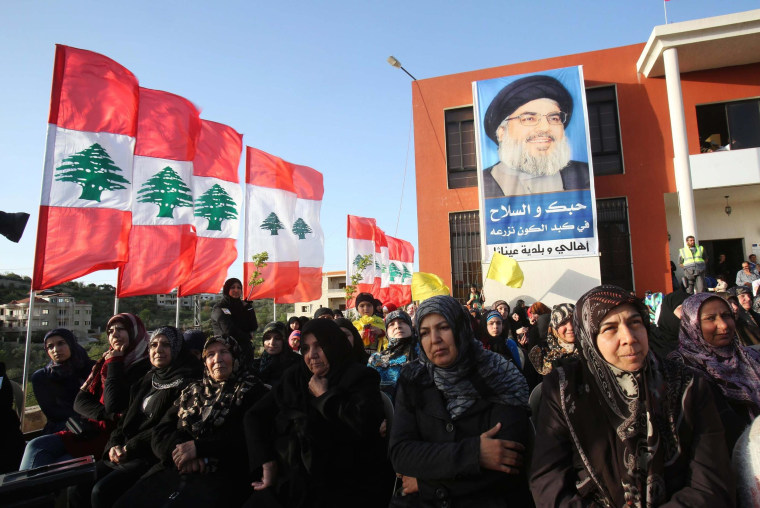 Image: Hezbollah supporters stand in front of a banner of their leader Nasrallah as they listen to his speech in Aineta