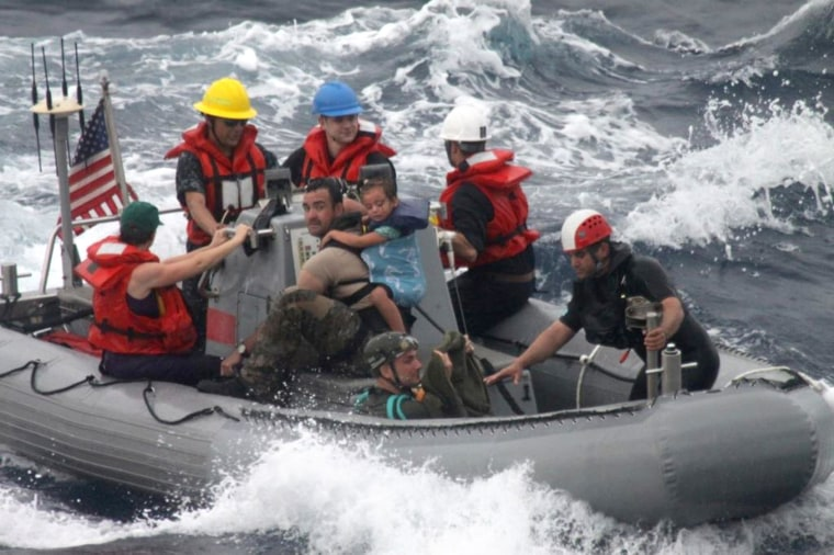 Image: Sailors assist in the rescue of a family with a sick infant via the ship's small boat as part of a joint U.S. Navy, Coast Guard and California Air National Guard rescue effort