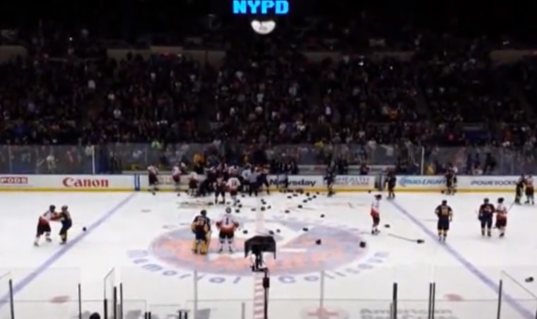 In this image taken from video provided by Ken Turnlund, players brawl during the second period of an annual charity hockey match between New York City police and firefighters Sunday, April 6, at Nassau Coliseum in Uniondale, N.Y. The NYPD eventually won 8-5.