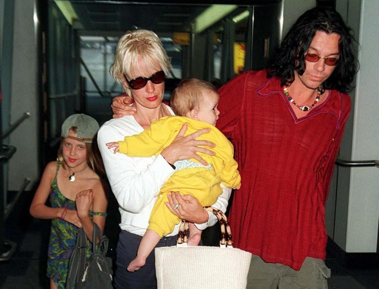 Michael Hutchence and Paula Yates, carrying Heavenly Hiraani Tiger Lily, with Peaches walking alongside at London's Heathrow Airport in 1997.
