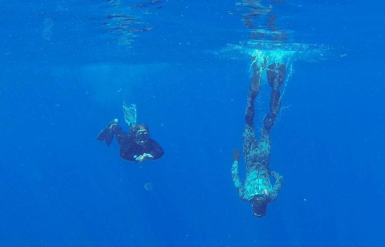 Able Seaman Clearance Divers Michael Arnold, left, and Matthew Johnston scan the water for debris.