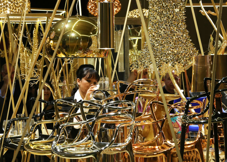 Image: A woman cleans chairs designed by Kartell, displayed at the Milan Design Fair, in Milan, Italy