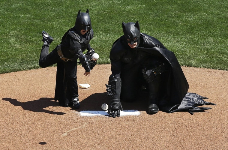 Image: Miles Scott, dressed as Batkid, throws the ceremonial first pitch