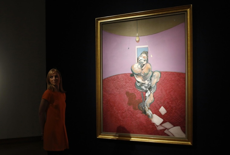 """A gallery assistant poses with """"Portrait of George Dyer Talking"""" by Francis Bacon in 1966 on display at Christie's in London February 7, 2014."""