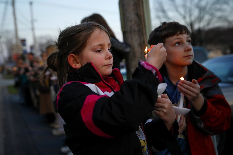 Ashlin, left, and Jude Burkhart, from Murrysville, hold candles during a prayer vigil for victims of the Franklin Regional High School stabbing rampage, at Calvary Lutheran Church in Murrysville, Pa., April 9, 2014.