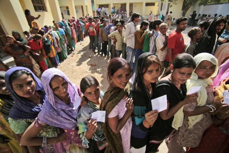 Indians stand in a queue to cast their votes outside a polling station during parliamentary elections in Jammu