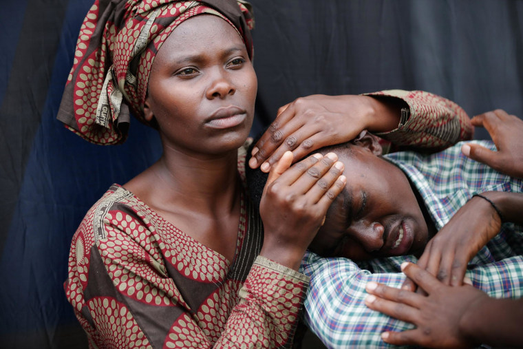 Image: A woman consoles Bizimana Emmanuel, 22, during the 20th anniversary commemoration of the 1994 genocide at Amahoro Stadium in Kigali, Rwanda