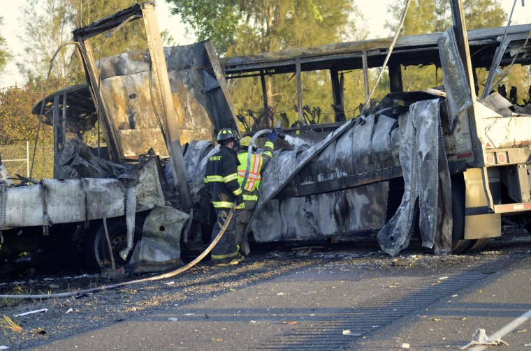 Image: Firefighters douse the wreckage at the scene of a collision between a tractor-trailer and a tour bus near Orland, Calif.