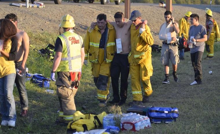 Image: Emergency personnel help a survivor after crash near Orland, Calif.