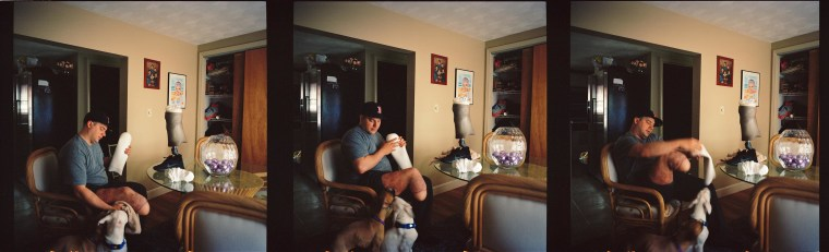 Boston Marathon Bombing survivors J.P. Norden puts on his prosthetic leg at home in Stoneham, Mass., Monday, April 7 2014,