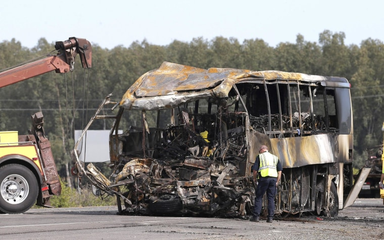 Image: A California Highway Patrol Officer looks over the burned out remains of a tour bus on Friday that collided with a FedEX truck on Interstate 5 Thursday in Orland, Calif.