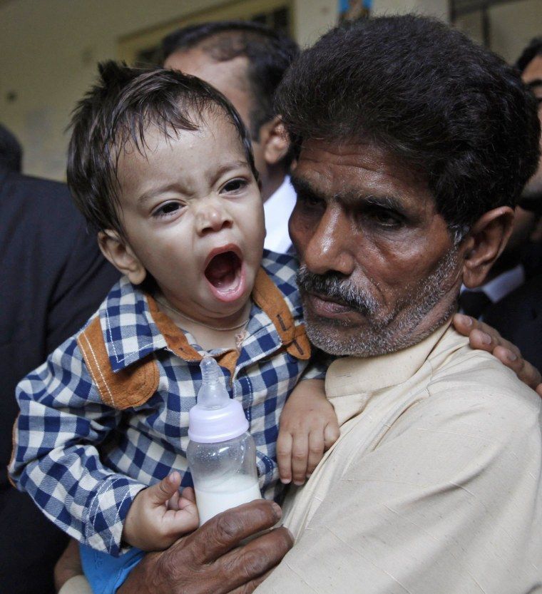 Image: Nine-month-old baby Musa Khan yawns while being carried by his grandfather Muhammad Yasin as they leave after appearing in a court in Lahore