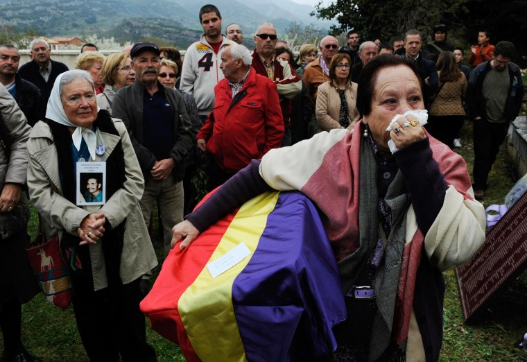 Image: Juana Gutierrez cries while holding the remains of her grandfather, a victim of Spain's Civil War, in the cemetery of Valdenoceda