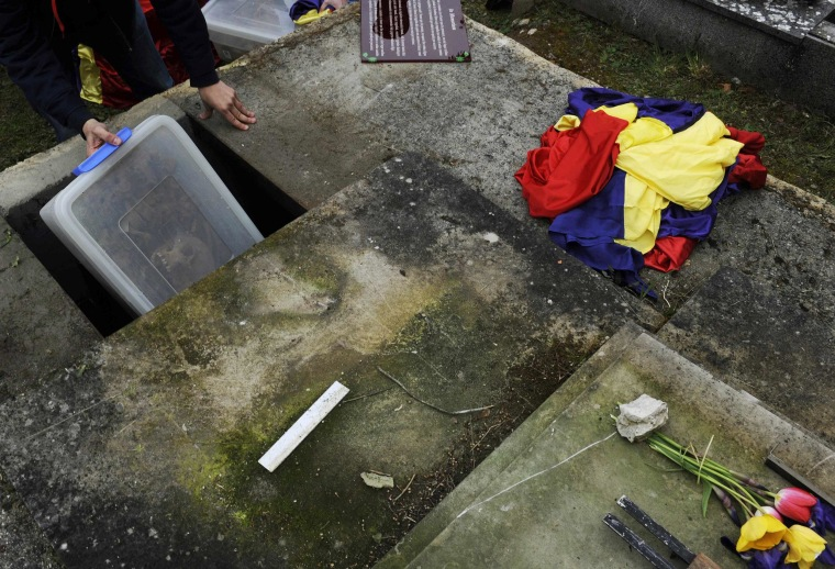 Image: A man takes the remains of a victim of Spain's Civil War for burial in a mausoleum at the Valdenoceda cemetery