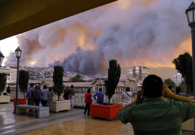 Image: People look at smoke from a forest fire in Valparaiso city, northwest of Santiago