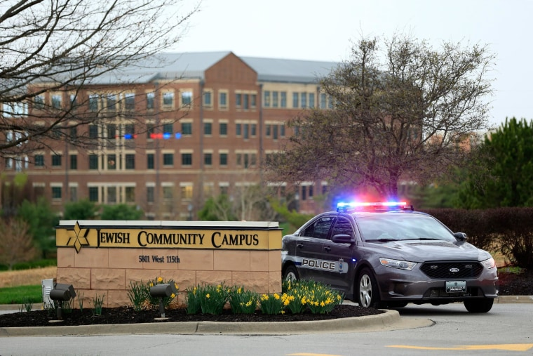 A police car sits at the entrance of the Jewish Community Center after three were killed when a gunman opened fire on April 13, 2014, in Overland Park, Kansas. Police arrested and were questioning a suspect.