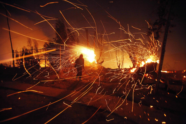 A person tries to extinguish flames as sparks fly during a forest fire in Valparaiso, Chile, early Sunday, April 13, 2014. Authorities say the fires have destroyed hundreds of homes, forced the evacuation of thousands and claimed the lives of at least seven people.