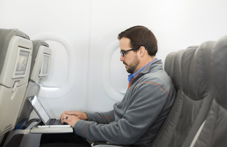 Image: A man uses his laptop on a plane