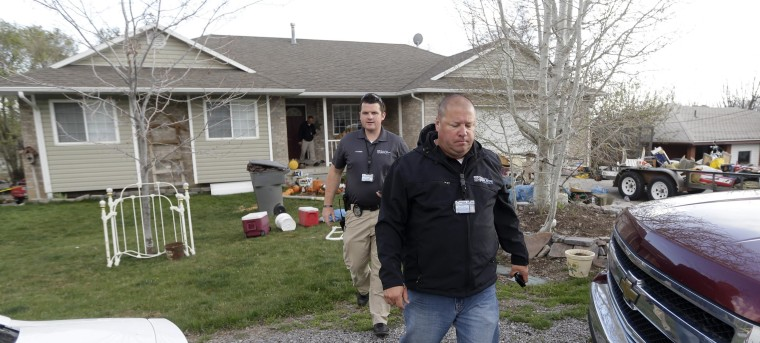 Pleasant Grove Police investigate the scene where seven infant bodies were discovered and packaged in separate containers at a home in Pleasant Grove, Utah, Sunday, April 13, 2014. According to the Pleasant Grove Police Department, seven dead infants were found in the former home of Megan Huntsman, 39. Huntsman was booked into jail on six counts of murder.