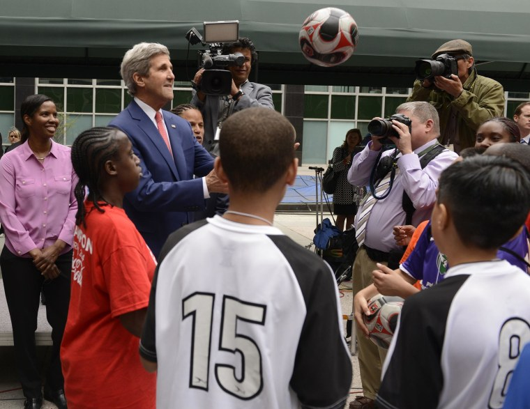 Image: U.S. Secretary of State Kerry plays catch with group of youth soccer players attending clinics taught by DC United players, prior to a ceremony for the start of the FIFA World Cup Trophy Tour, at the State Department in Washington
