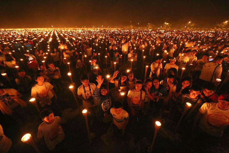 Image: Tens of thousands of participants stand beside bamboo torches using candles to form a message of peace.