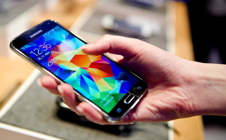 A woman holds the new Samsung Galaxy S5 smartphone at the Vodafone exhibition stand at the CeBITfair in Hanover, Germany, on March 11.