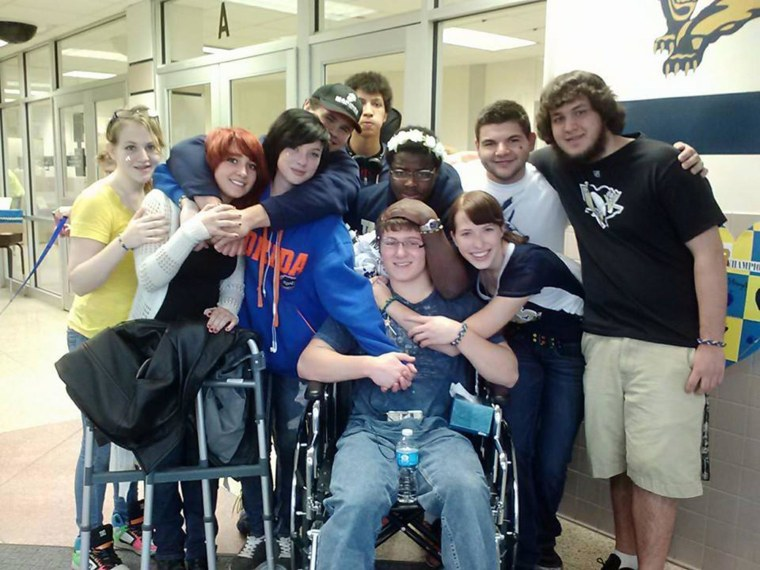 Students pose for a group photo after returning to Franklin Regional High School outside Pittsburgh on April 15, 2014. During a bloody knife attack at the school, Brett Hurt, in the wheelchair at center, jumped in front of Gracey Evans, behind the camera, and was stabbed in the back.