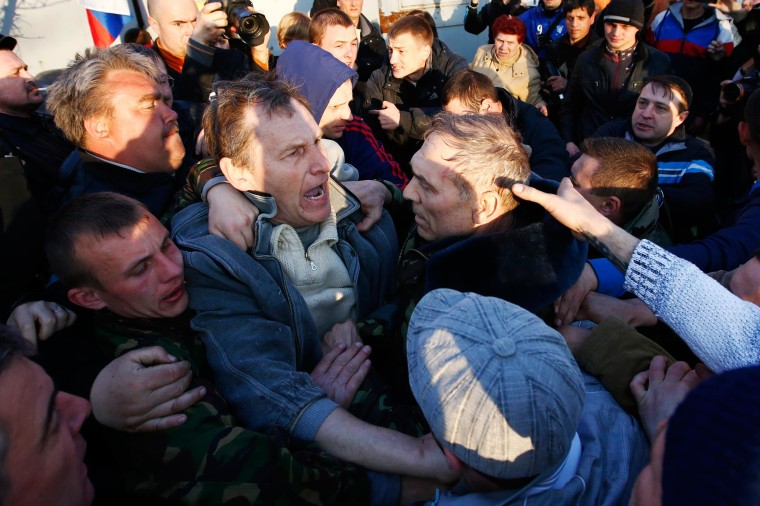 Image: Pro-Russia protesters rough up Krutov in front of a Ukrainian airbase in Kramatorsk