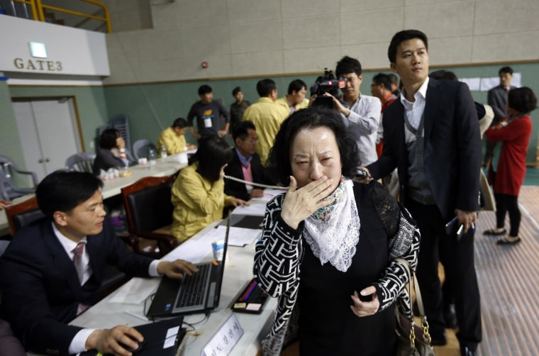 Image: The mother of a passenger aboard the ferry finds her son's name on list of survivors