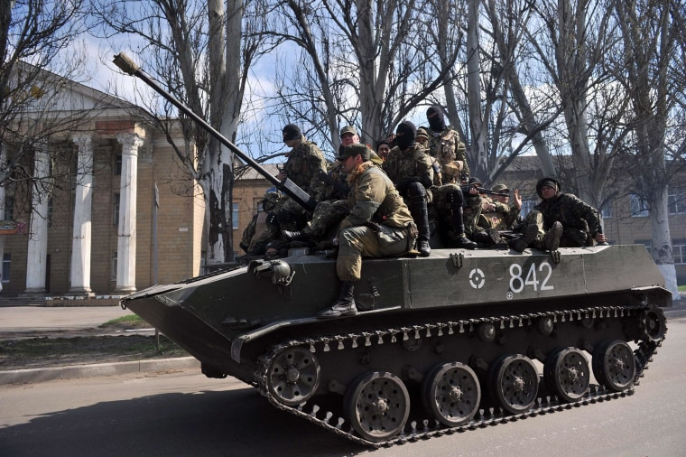 Image: Men wearing military fatigues ride on an armored personnel carrier in the eastern Ukrainian city of Slavyansk