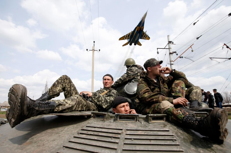 Image: A fighter jet flies above as Ukrainian soldiers sit on an armoured personnel carrier in Kramatorsk