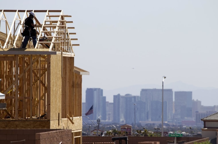 Carpenters work on new homes in Las Vegas.  Groundbreaking ion new homes rose less than expected in March and building permits fell.