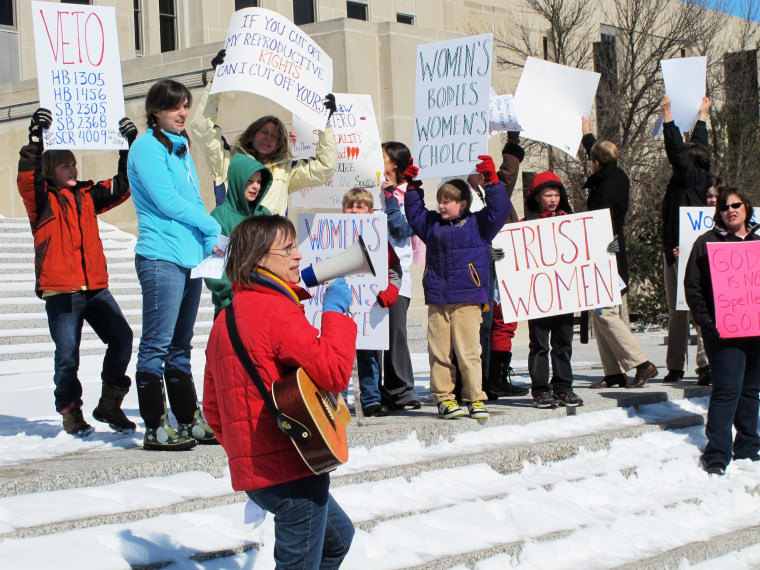 Image: A woman, left, leads a chants at an abortion-rights rally at the state Capitol in Bismarck, N.D.