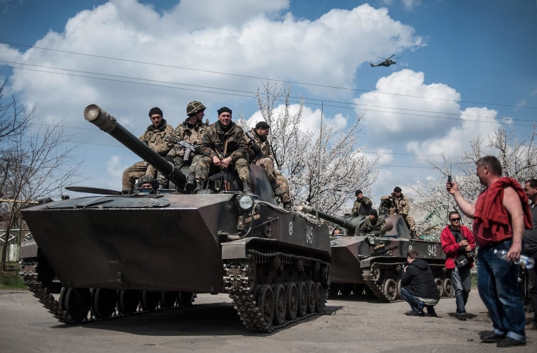 Image: Pro-Russian protesters take photos of Ukrainian soldiers sitting on their armored vehicle in Kramatorsk, Ukraine