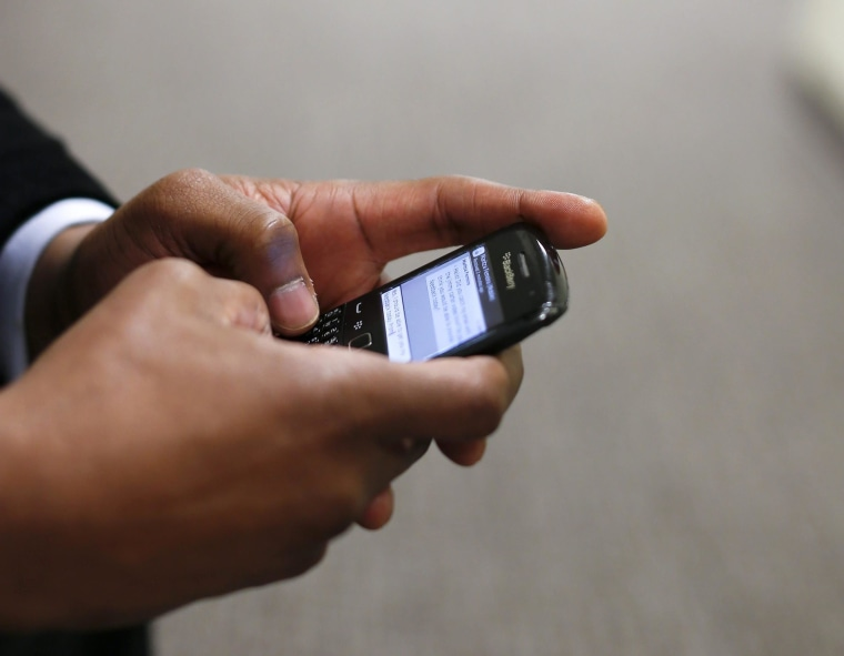 Image: A man uses his Blackberry mobile device to write a text message