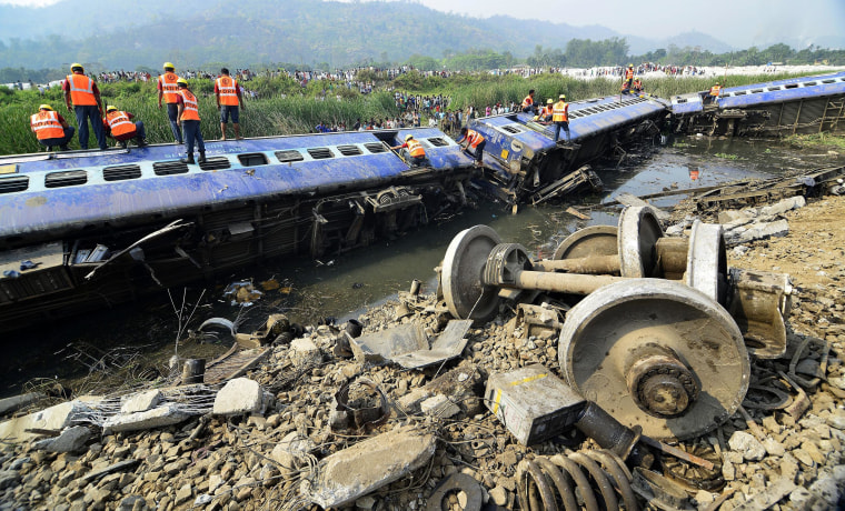 Railway workers inspect the derailed carriages of a passenger train at Jagiroad Railway Station, about 56 miles away from Guwahati, India, on April 16.