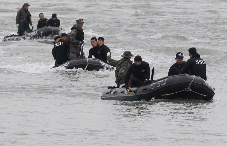 Image: Members of the South Korean Navy search for missing passengers