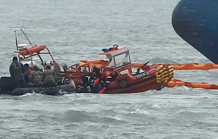 Image: South Korean Coast Guard rescue teams retrieve the body of a dead passenger