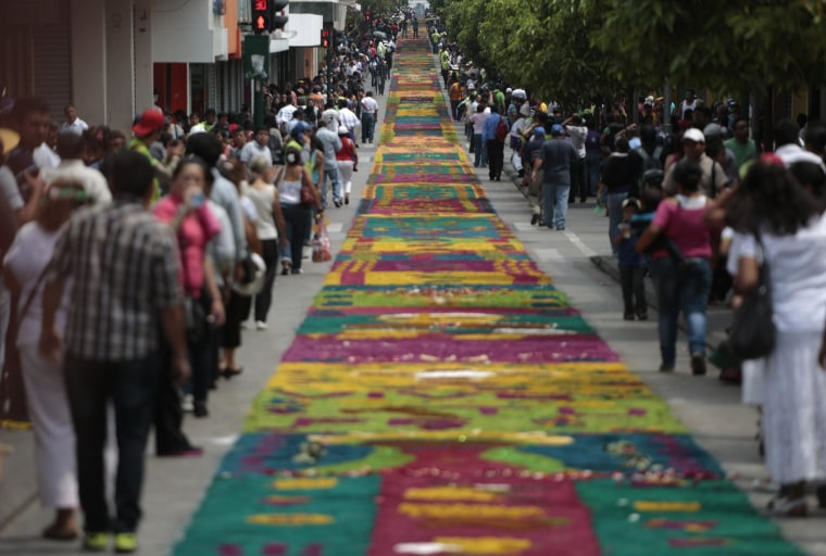 Image: People walk next to a traditional Guatemalan traditional sawdust carpet during Holy Week celebrations, in downtown Guatemala City