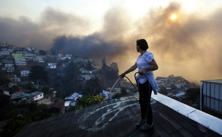 A woman sprays water on the roof of her home on Ramaditas Hill in Valparaiso, Chile, on April 13. Fed by high temperatures and strong winds, the flames moved from forest areas at the top of the hilly city on Saturday night and destroyed large swaths of predominantly low-income, wooden houses.