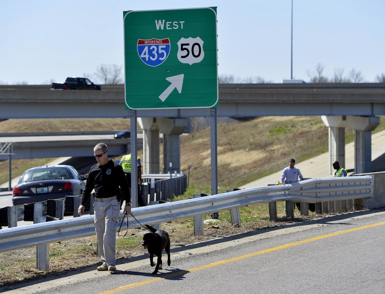 Kansas City police and agents from the Alcohol, Tobacco and Firearms with canines investigated a shooting along southbound Interstate 435 in Kansas City, Mo., Wednesday, April 9, 2014. Police have connected 12 shootings targeting vehicles on Kansas City-area roads and highways since early March.