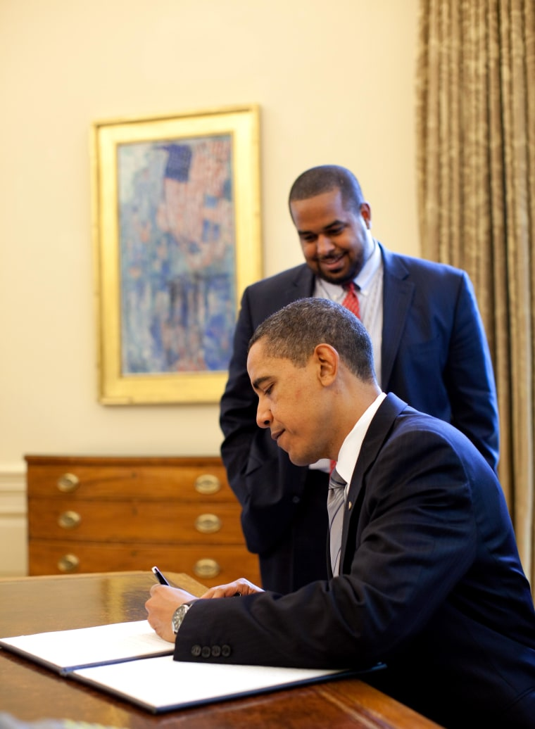 President Barack Obama signs the proclamation marking the National Day of Prayer May 7, 2009.  Looking on is Joshua DuBois, Director of the White House Office for Faith-Based and Neighborhood Partnerships.  Official White House Photo by Pete Souza