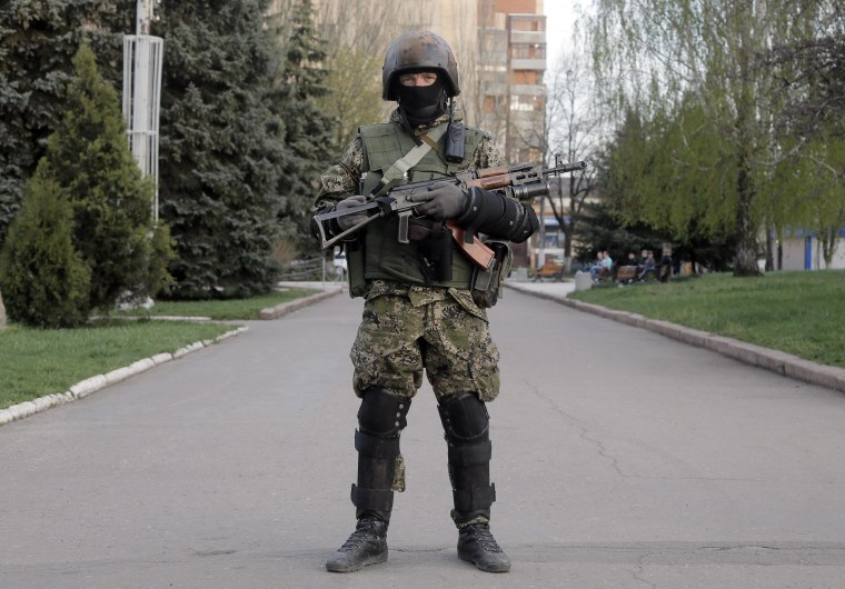 A pro-Russian gunman patrols a streets in downtown Slovyansk, eastern Ukraine, Friday, April 18, 2014. Dashing hopes of progress raised by a diplomatic deal in Geneva, pro-Russian insurgents who have occupied government buildings in more than 10 Ukrainian cities said Friday they will not leave them until the country's interim government resigns. (AP Photo/Efrem Lukatsky)