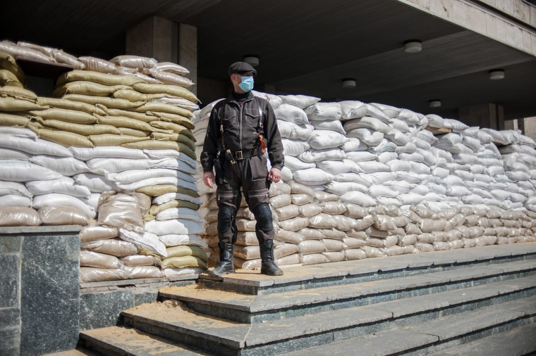 Image: A pro-Russian protester stands in front of a barricaded police station in Slaviansk, Ukraine, on April 18, 2014.
