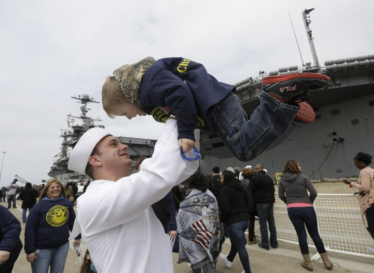 Image: Kollia Safford is lifted by his godfather, Communications Specialist, Christopher Payne, after he disembarked from the nuclear aircraft carrier Harry S. Truman