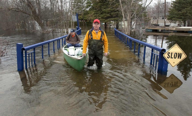 Image: Residents Joe Keating and his son Joe junior use hip waders and canoe on Willow Road to get out along flooded Otonabee River near Peterborough Ontario.