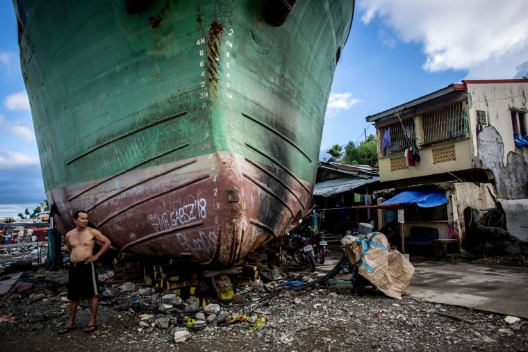 Image: A man stands in front of a large ship grounded by Typhoon Haiyan in Tacloban, Leyte, Philippines