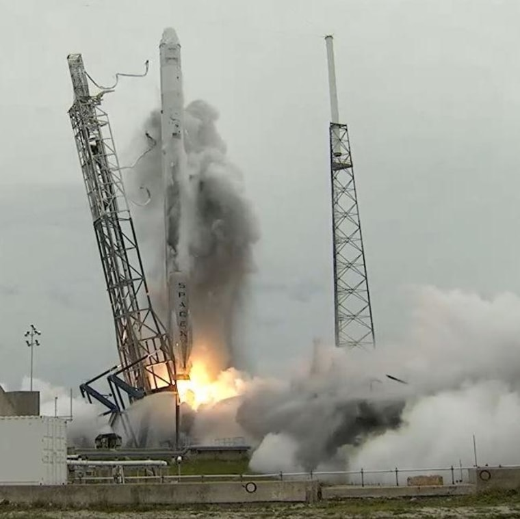 A dark plume sprays up the side of SpaceX's Falcon 9 rocket during Friday's launch, leaving a black stain behind. SpaceX CEO Elon Musk said the stain came from dirty water that had been spread over the Cape Canaveral pad before liftoff.